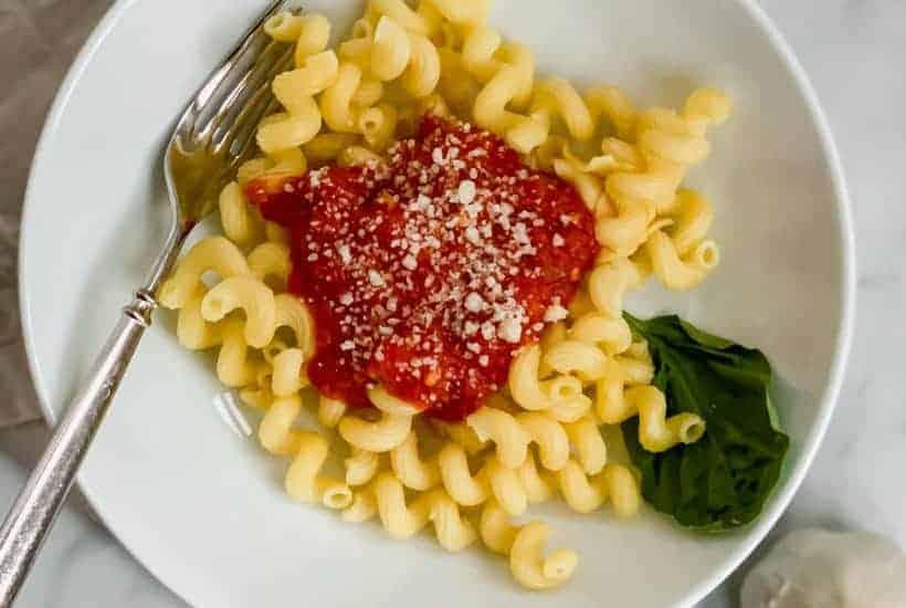 Homemade Tomato Sauce with a kick on top of fusilli pasta in white bowl on a khaki napkin