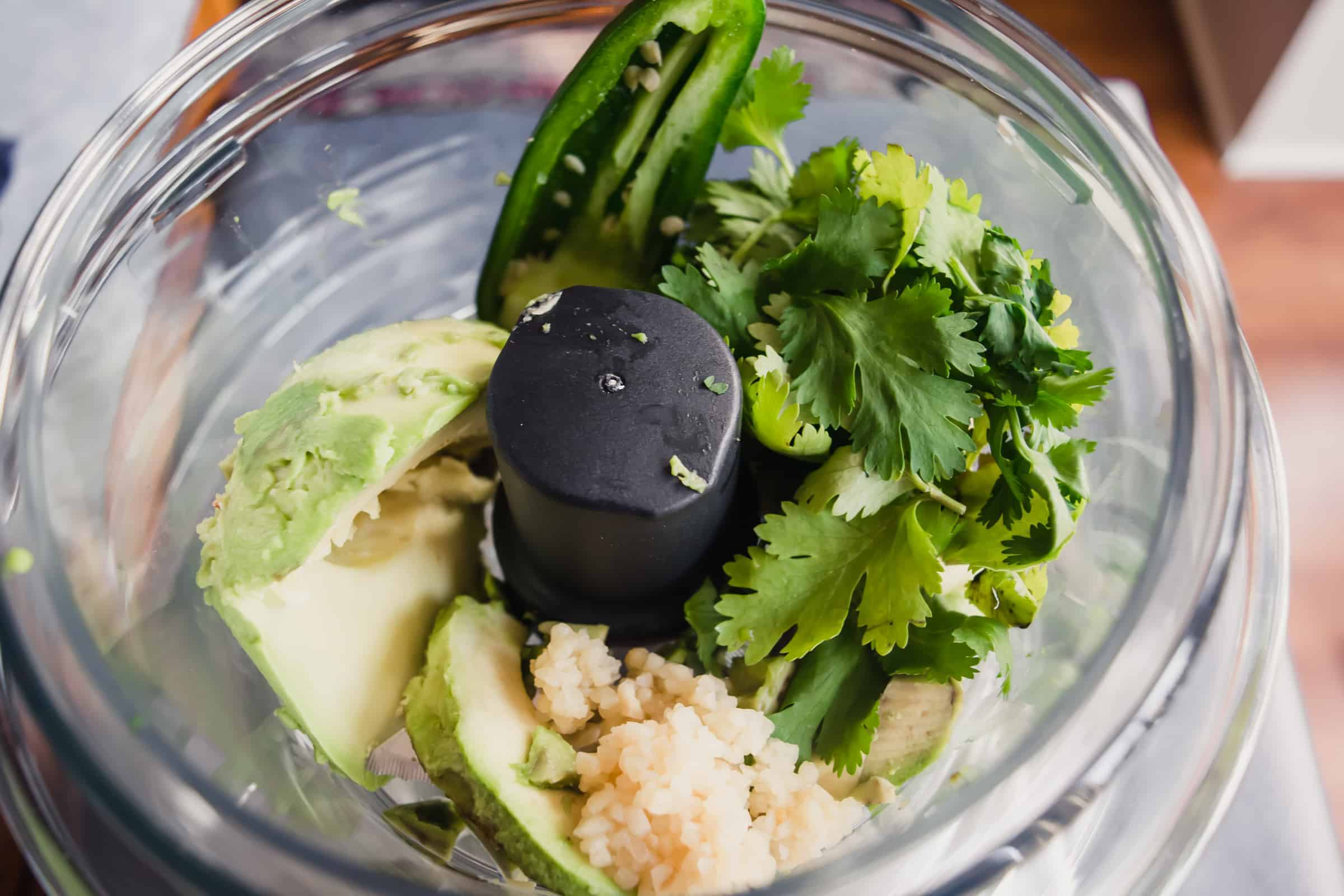 food processor with avocado, cilantro, jalapeno, lemon, garlic