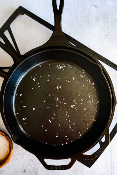 overhead shot of cast iron skillets on a stove grate with a wooden bowl of salt