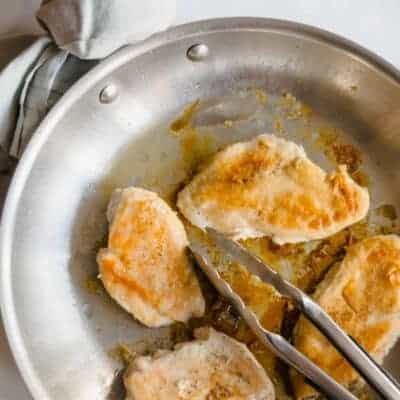 cooked chicken breasts in a skillet with tongs and a light blue napkin