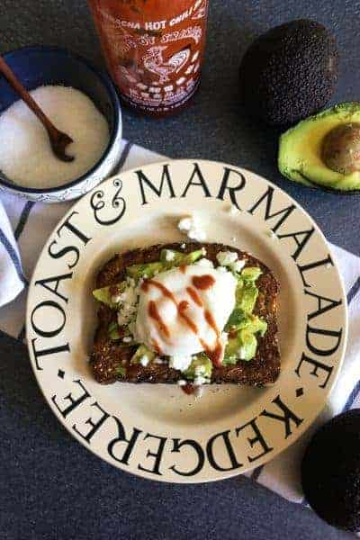 avocado toast with a poached egg and sriracha on top with salt and an egg in the background.