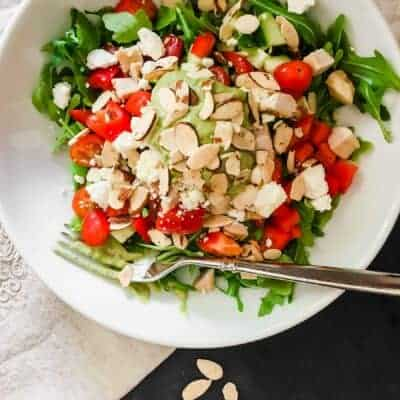 white bowl with greens, tomatoes, feta, almonds, chicken and avocado cilantro dressing