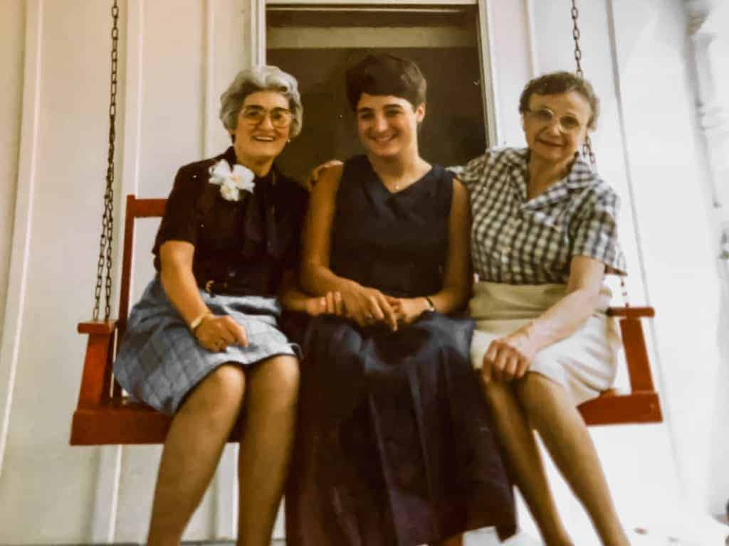 grandmas and a girl in a blue dress on a red swing.