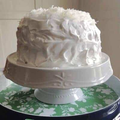 coconut cake on a white cakestand in a green and white flowered blue tray