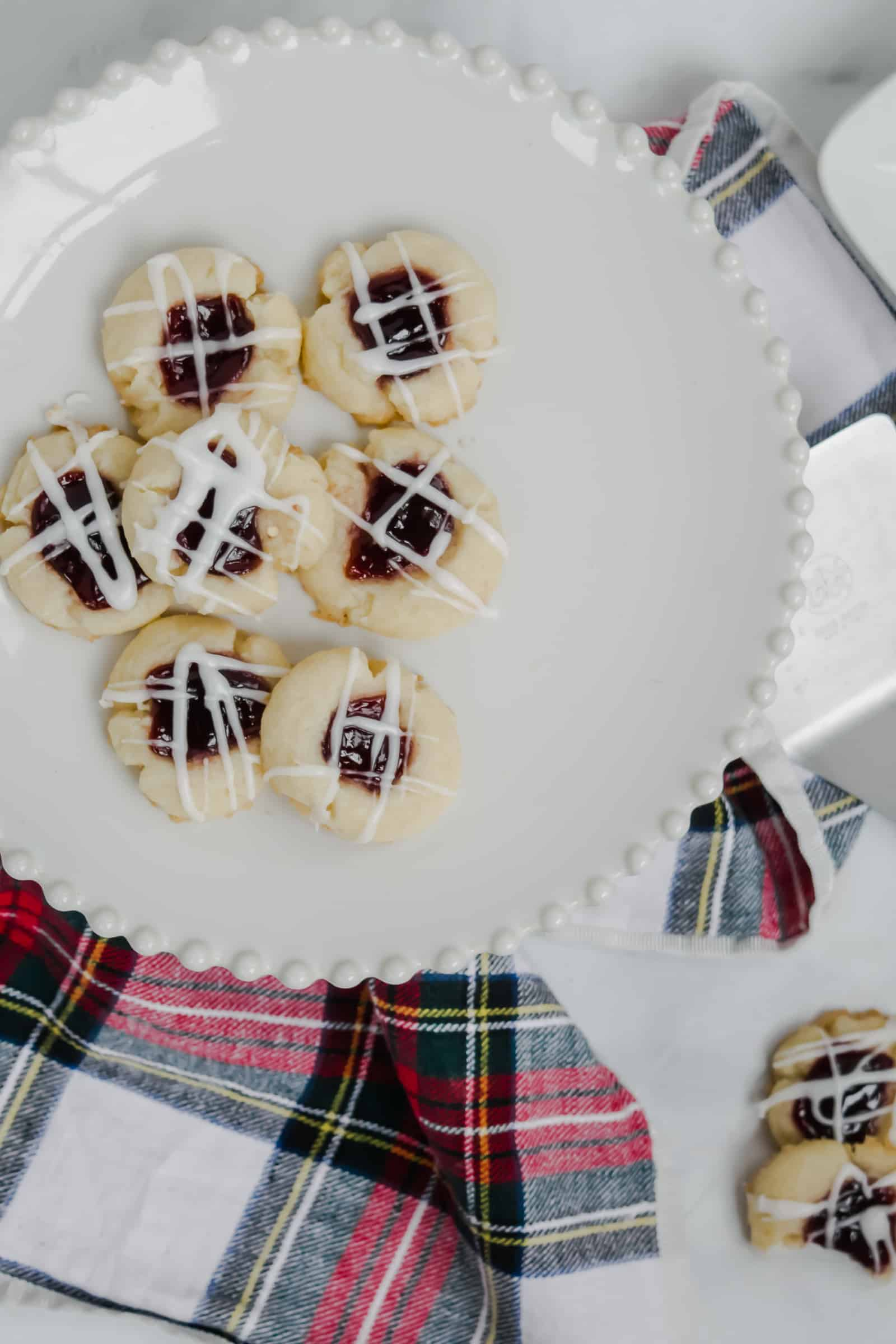 raspberry almond thumbprints on a white pedestal with a red and white plaid napkin and plates of cookies