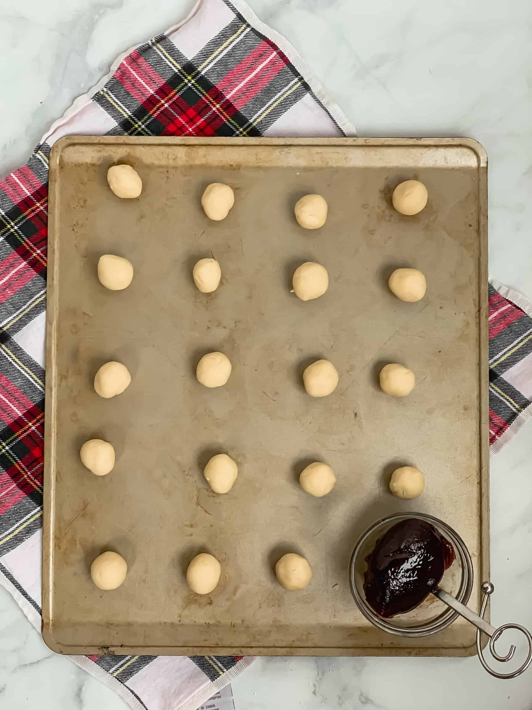 balls of cookie dough on a baking sheet with a bowl of raspberry jam in the lower corner all on top of a white and red plaid napkin and a marble background