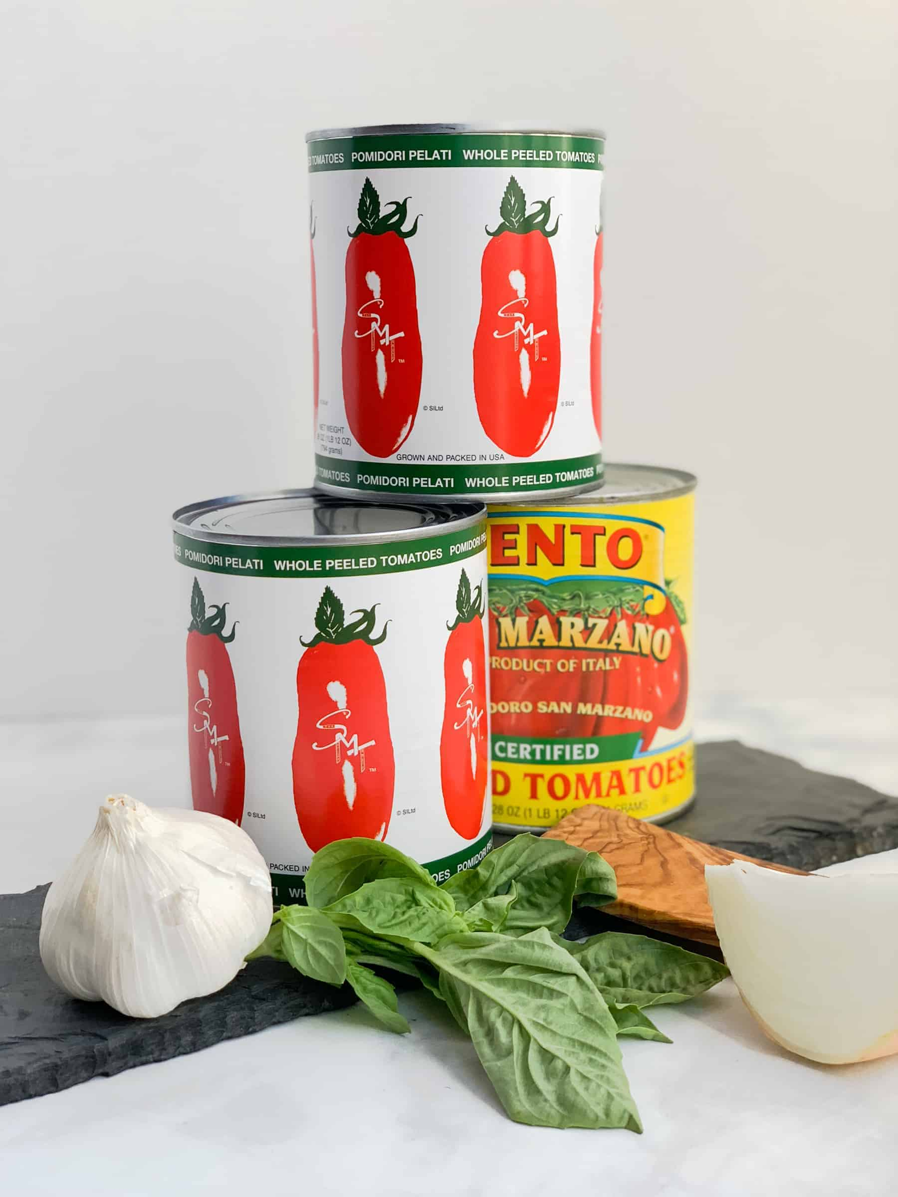 San Marzano Canned Tomatoes on slate with garlic and onion