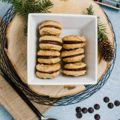 white bowl of chocolate ganache filled peanut butter cookies on a wooden piece of bark with a spoon of peanut butter and plaid dish