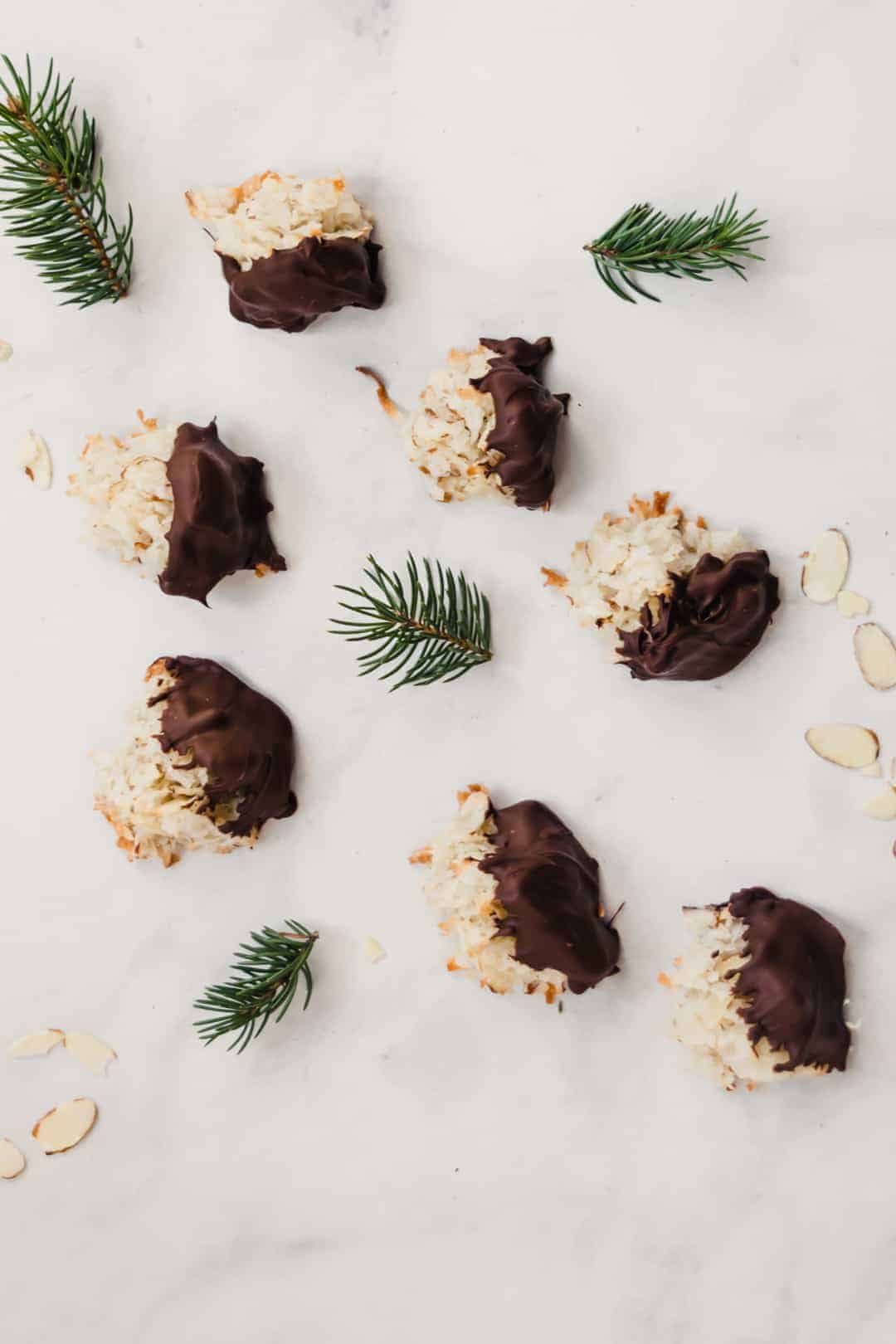 Coconut Macaroons dipped in chocolate with almonds and pine sprigs on marble