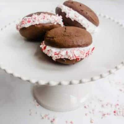 three peppermint mallow whoopie pies on a white pedestal