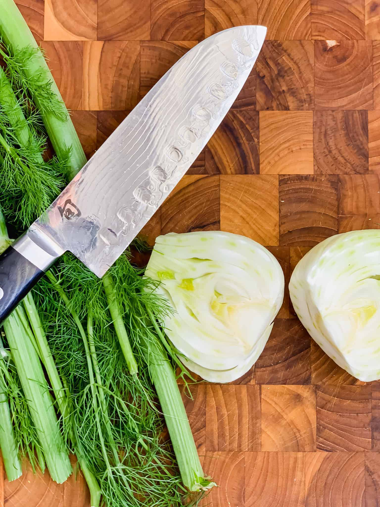 Fennel bulb sliced in half with knife on board