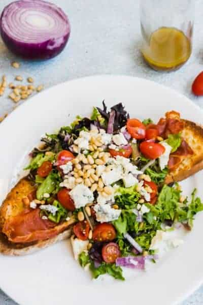 piece of toasted garlic bread with prosciutto, salad, blue cheese, tomatoes and red onions on top on a white plate with a fork and knife and some pine nuts