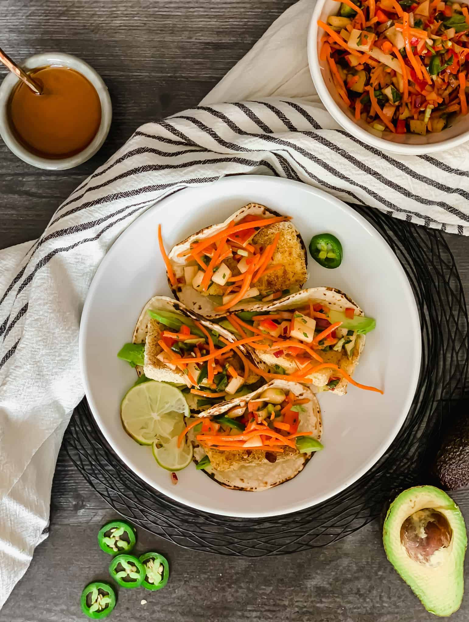 fish tacos with jalapeno carrot slaw and dressing and avocado on weathered board
