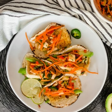four fish tacos on plate with lime and jalapeno apple carrot slaw with black and white towel.