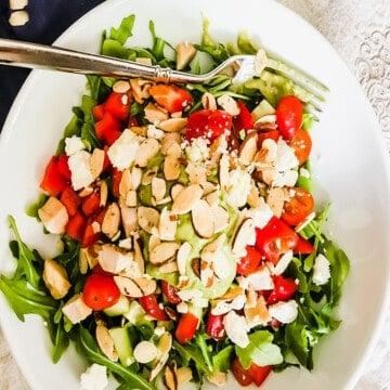 white bowl with greens, tomatoes, feta, almonds, chicken and avocado cilantro dressing.