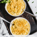 macaroni and cheese in two white bowls on a dark tray with a blue napkin and some parsley