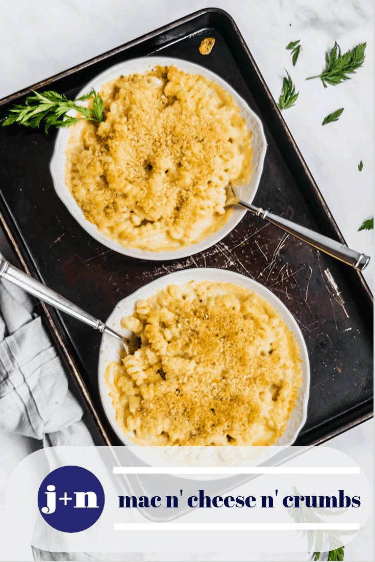 two gratin dishes of macaroni and cheese on a dark baking sheet with forks and a gray napkin and carrot leaves