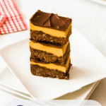 a stack of nanaimo bars on white plate with red gingham napkins in the foreground and background