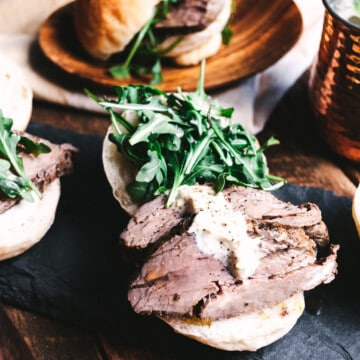 Beef tenderloin sandwiches on slate and wooden plates with a moscow mule in a copper mug