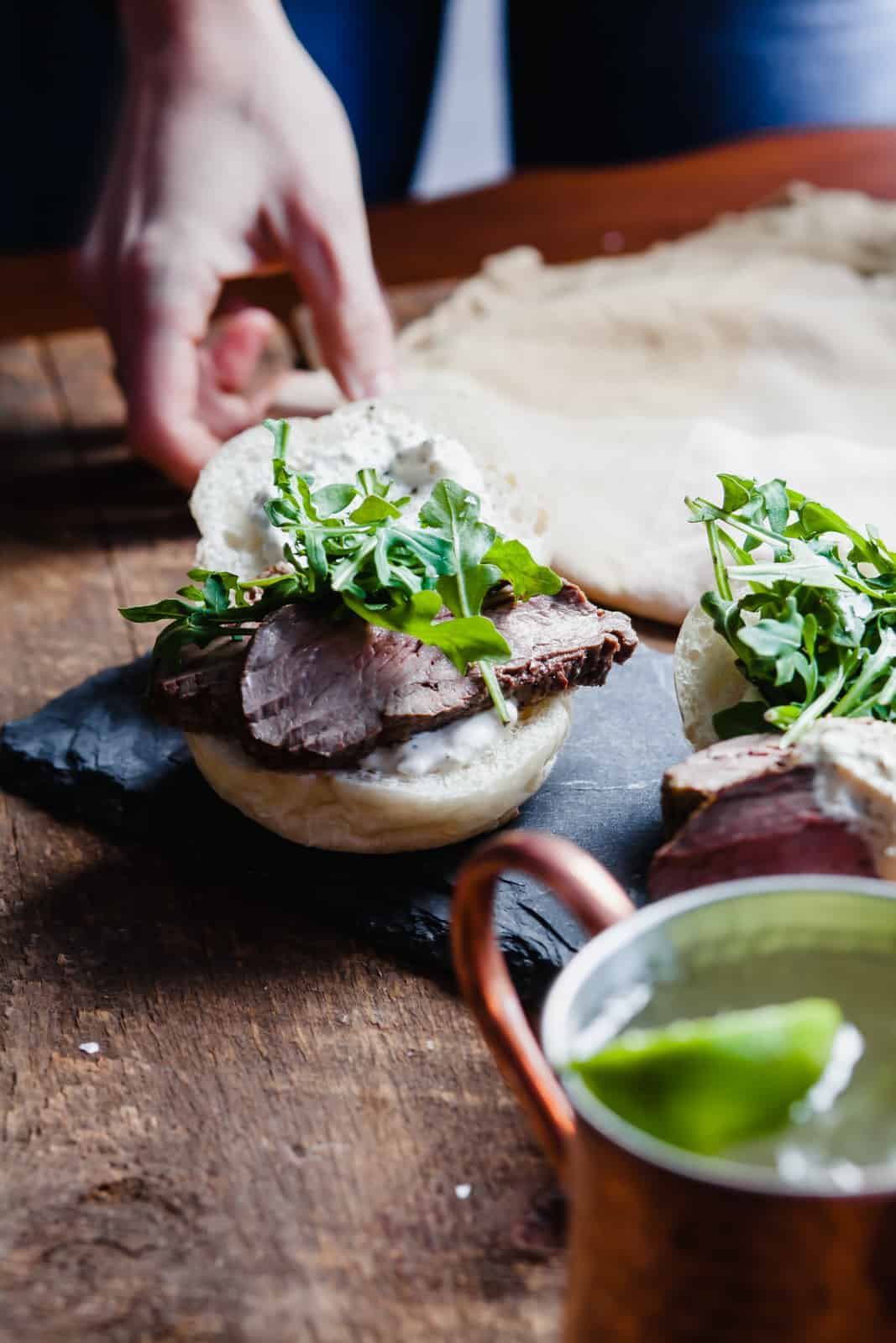 Person setting a table with a beef tenderloin sandwich and a Moscow mule in a copper mug on a wooden table