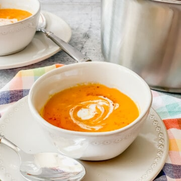two bowls of carrot ginger soup on gray plates and plaid napkin with a stainless soup pot