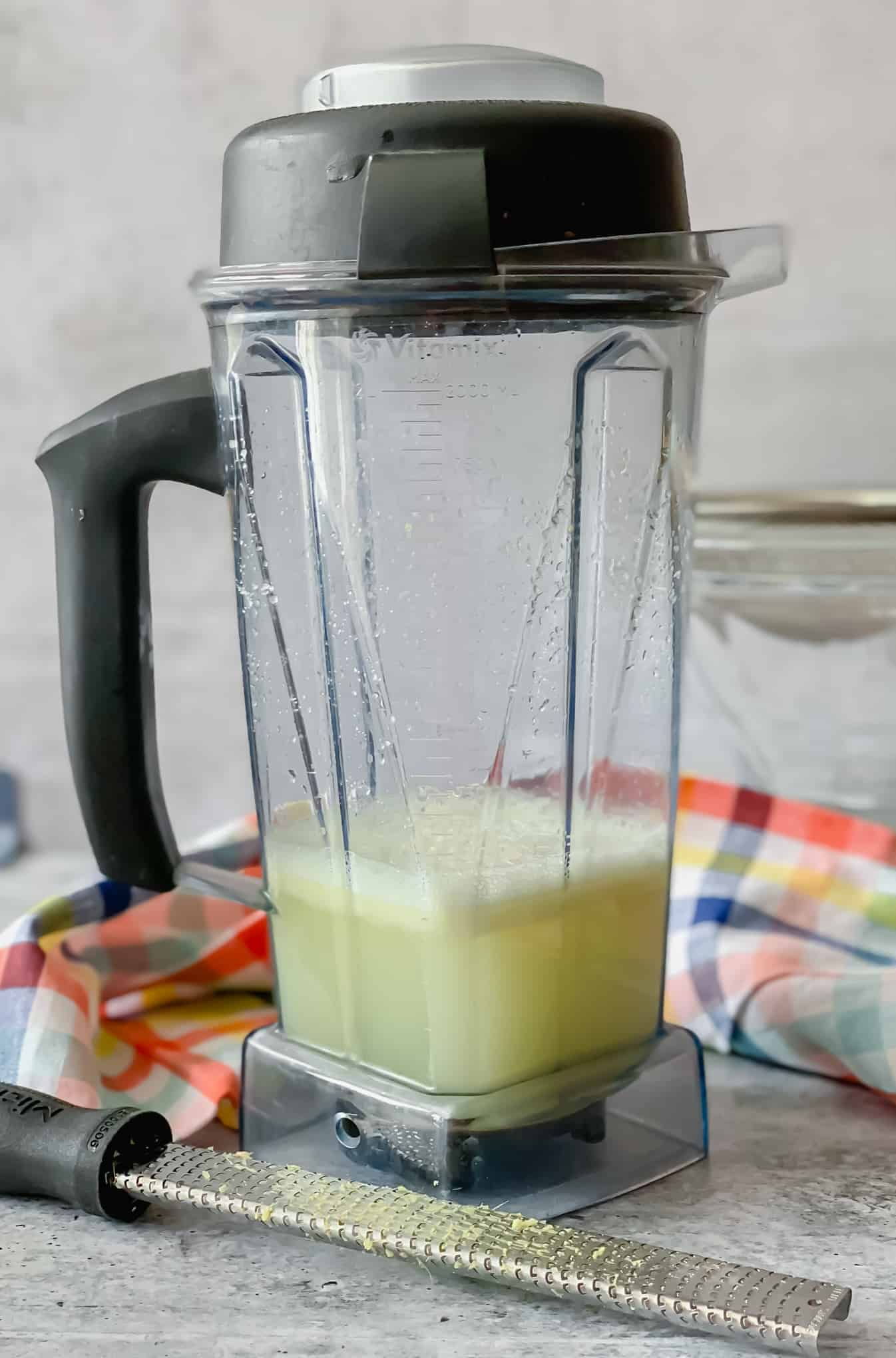 blender with ginger tea and zester on a bright plaid napkin