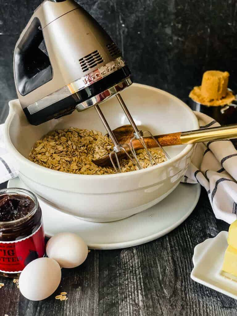 bowl of oats with a hand mixer, eggs, jar of fig butter, brown sugar and butter.