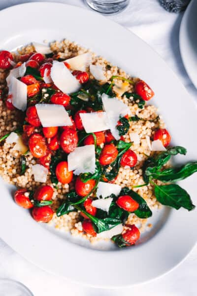close up of couscous with tomatoes and basil on a white platter