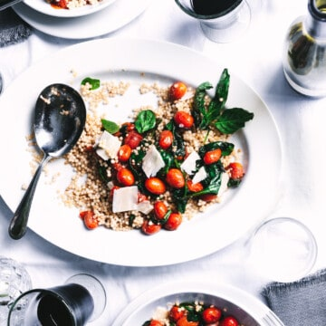 three plates of couscous with tomatoes and basil with two glasses of red wine all on a white tablecloth.
