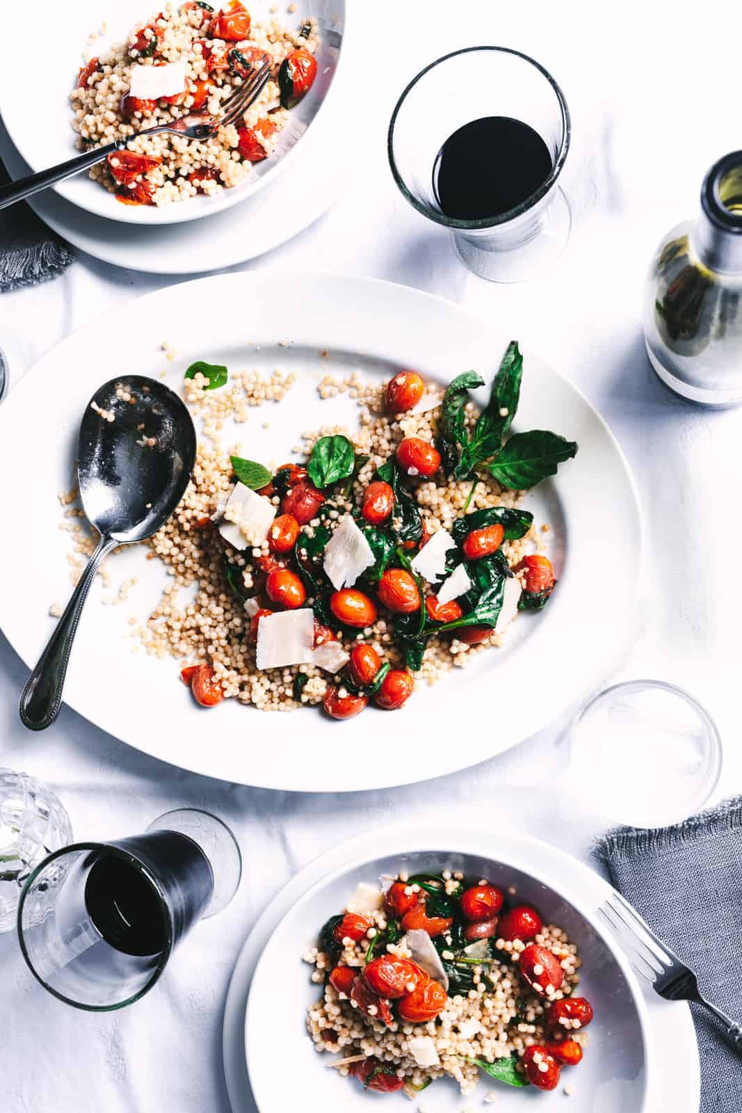 three plates of couscous with tomatoes and basil with two glasses of red wine all on a white tablecloth