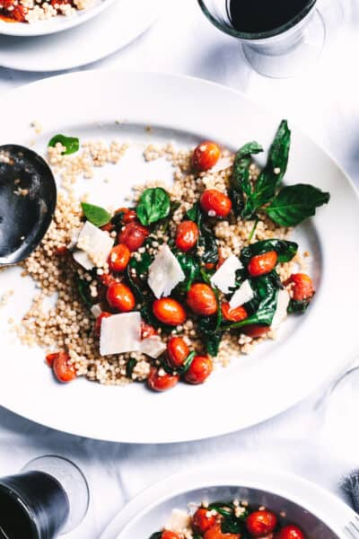 closeup of couscous with tomatoes, basil and parmesan on top and two glasses of wine