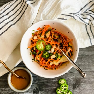 white bowl with grated carrots, diced apples and jalapenos with dressing and a white and black striped dish towel on a gray wooden background.