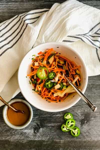 white bowl with grated carrots, diced apples and jalapenos with dressing and a white and black striped dish towel on a gray wooden background