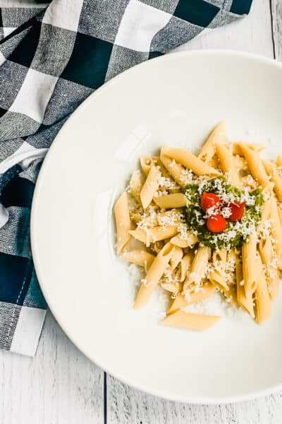 chickpea pasta with pesto and sweet peppers in a white bowl and a gingham napkin
