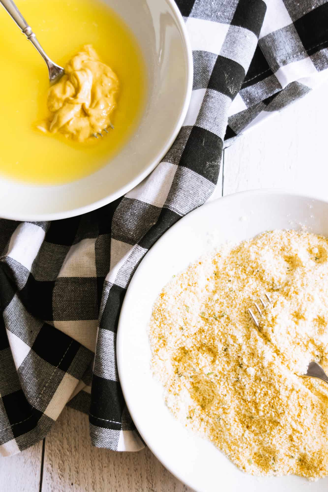 melted butter with Dijon mustard in a white bowl with parmesan and breadcrumbs in a white bowl on a black checkered napkin