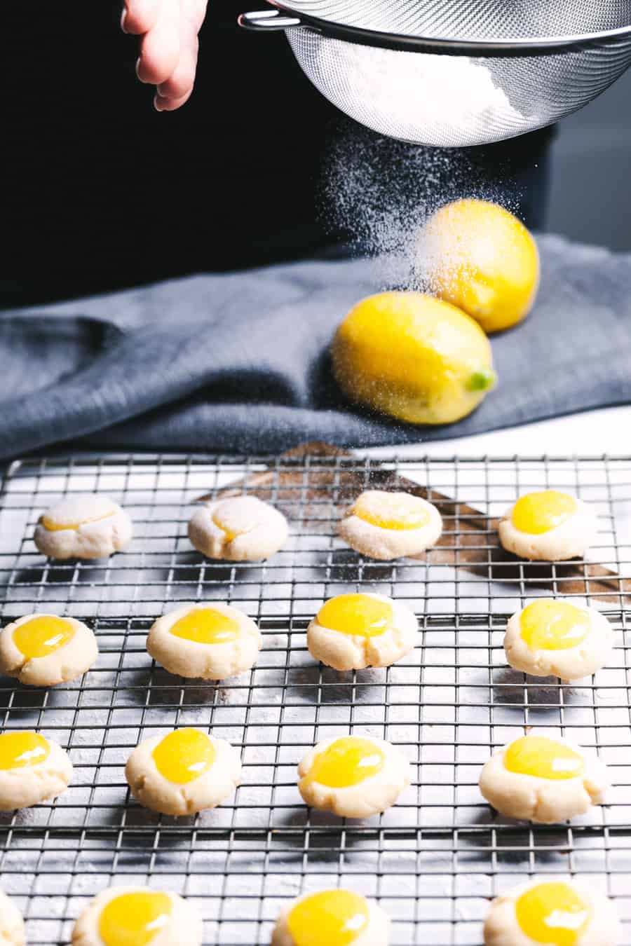 hands shaking a strainer of flour sprinkling lemon cookies on a wire rack.