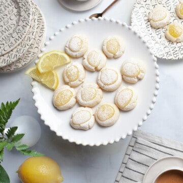 lemon cookies on a cake plate with two cups of coffee, plates and a striped towel and a lemon