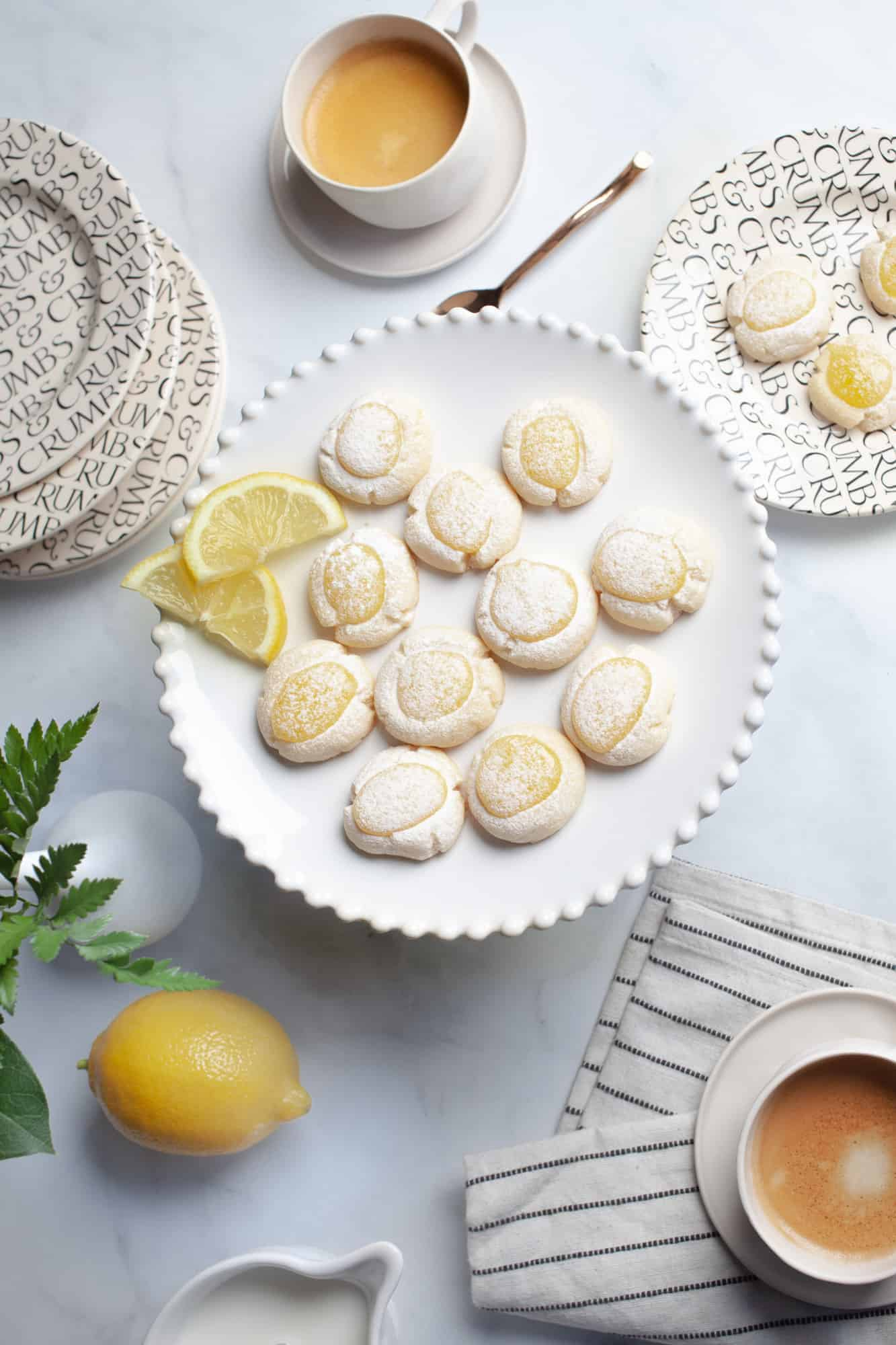 plate of lemon filled cookies with two cups of coffee and a lemon and black and white dishes