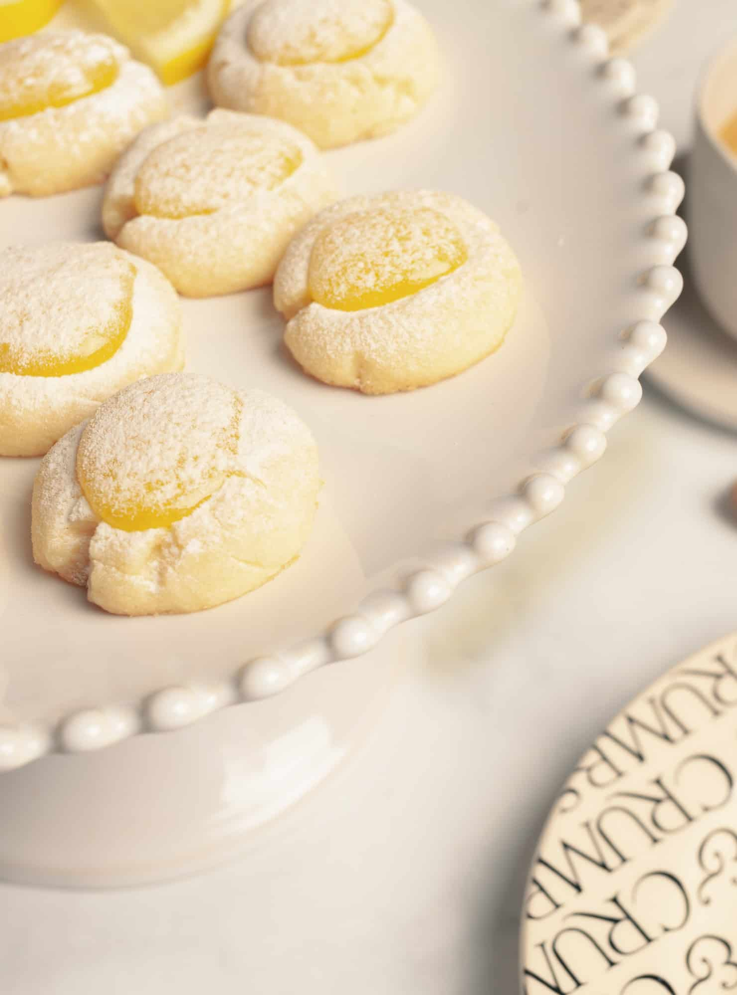 closeup of lemon thumbprint cookies on a white pedestal plate