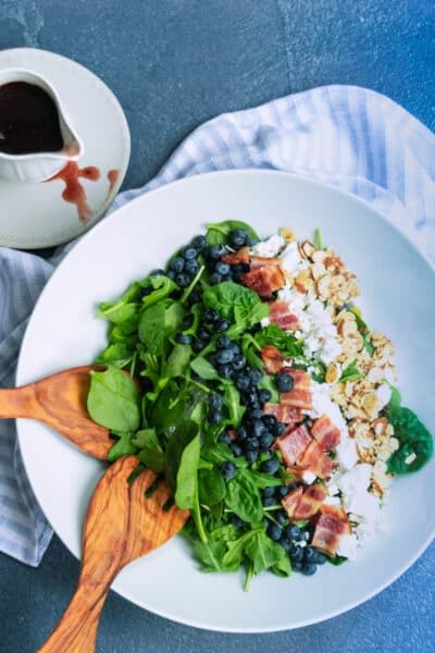 white bowl of salad with blueberries, feta, bacon and almonds and a white carafe of dressing