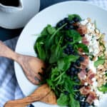 blueberries, cheese and greens and salad in a white bowl with wooden salad forks