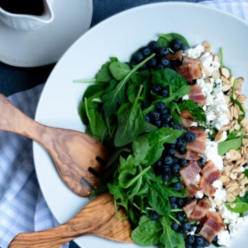 blueberries, cheese and greens and salad in a white bowl with wooden salad forks.