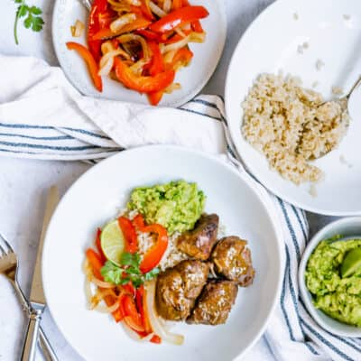 overhead of white bowl with carnitas, red peppers and onions, rice and guacamole