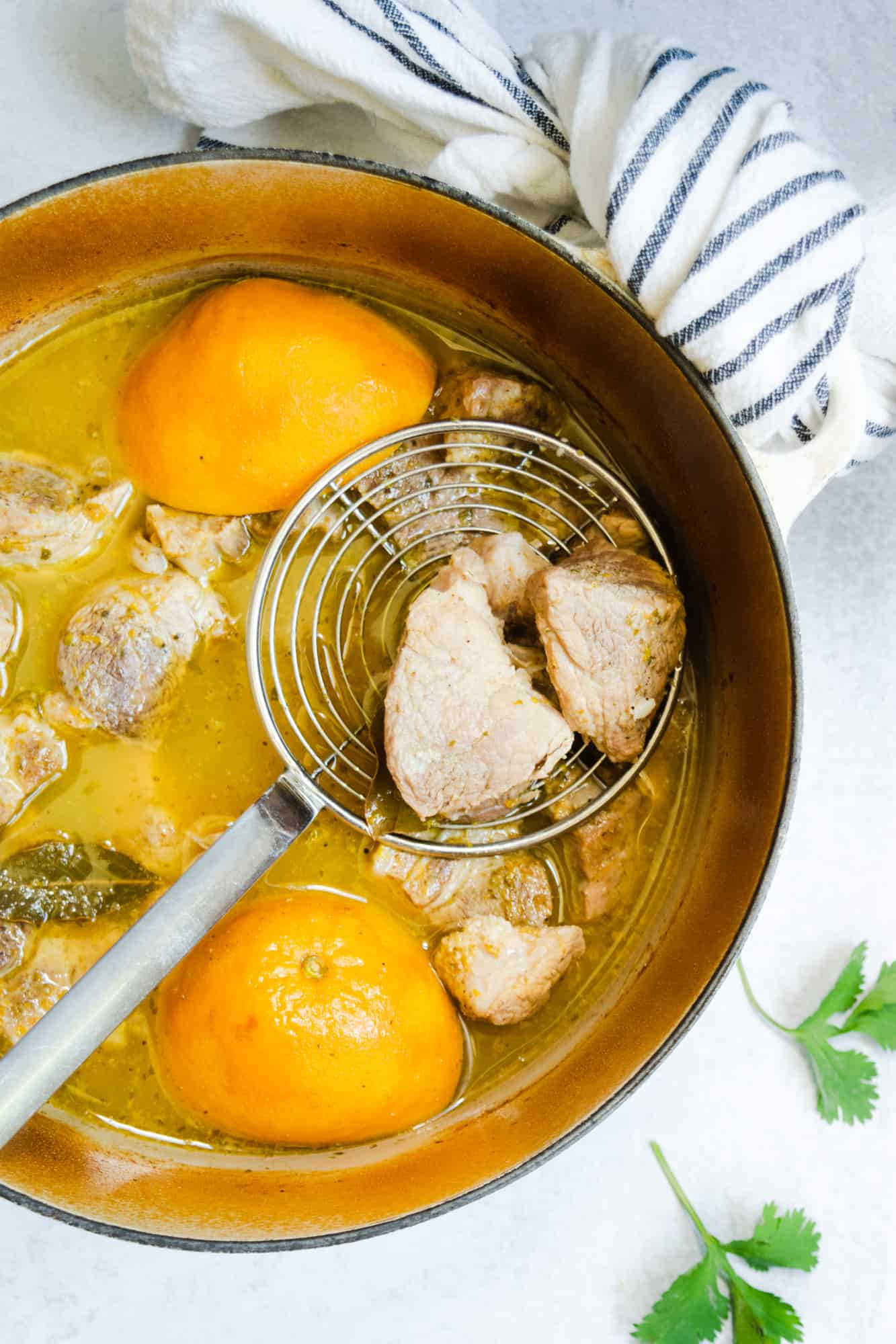 cooked pork carnitas with a skimmer in a pot of oranges and pork