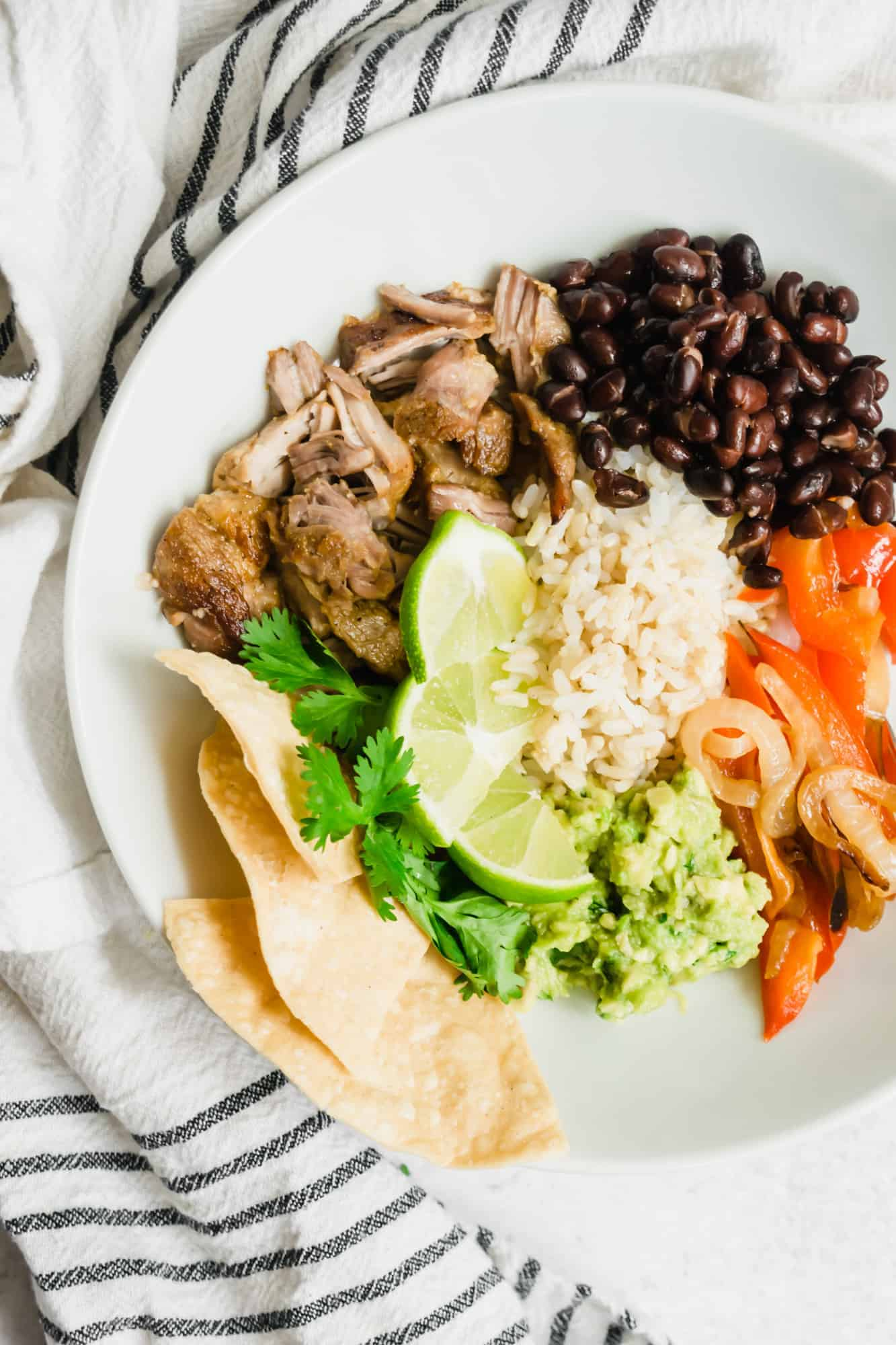 overhead of white bowl with carnitas, red peppers and onions, rice, black beans and guacamole