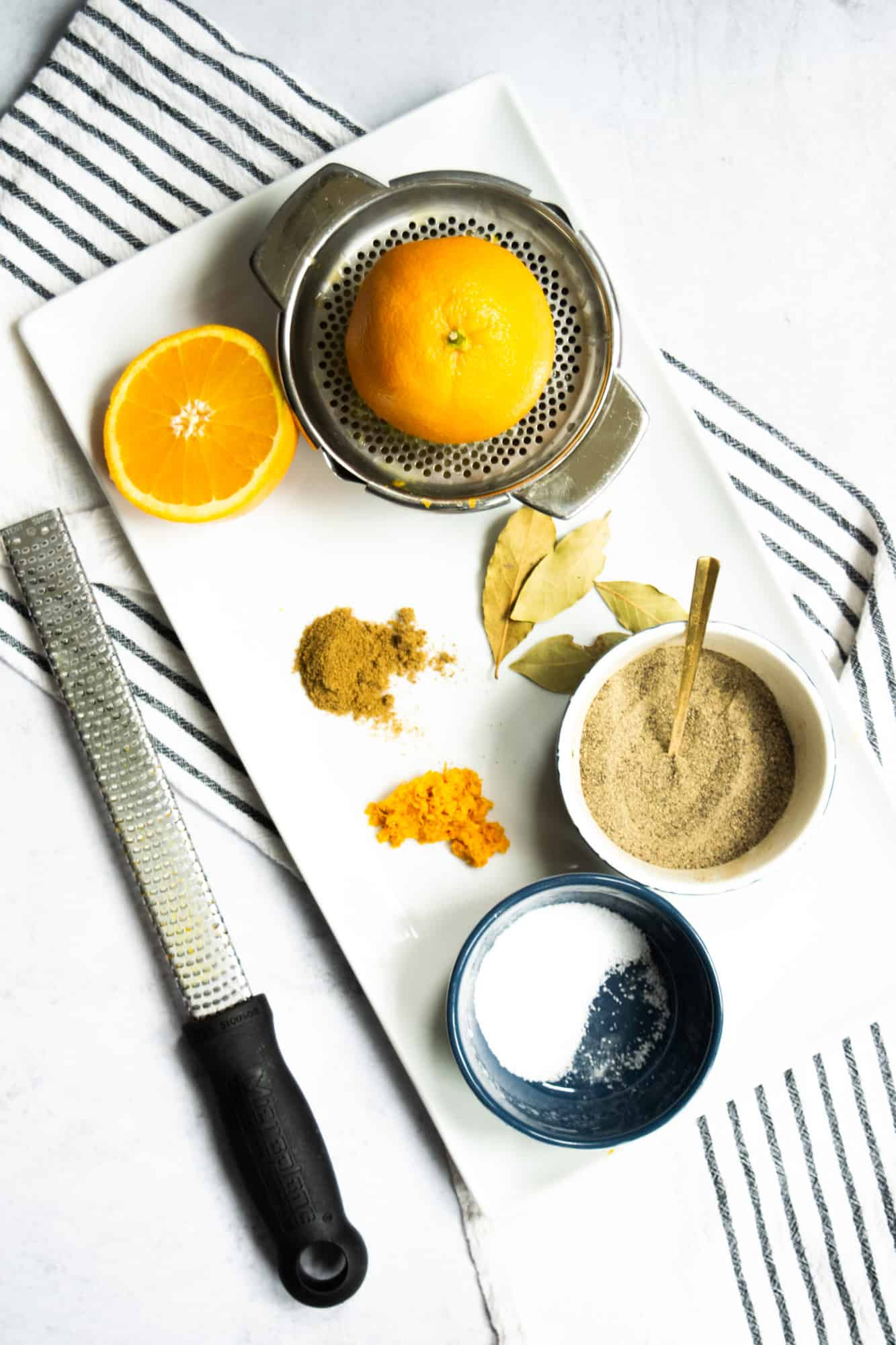 ingredients to make carnitas oranges, cumin, salt, pepper and bay leaves