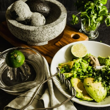 guacamole ingredients in a molcajete with avocados, cilantro, limes and a blue napkin.