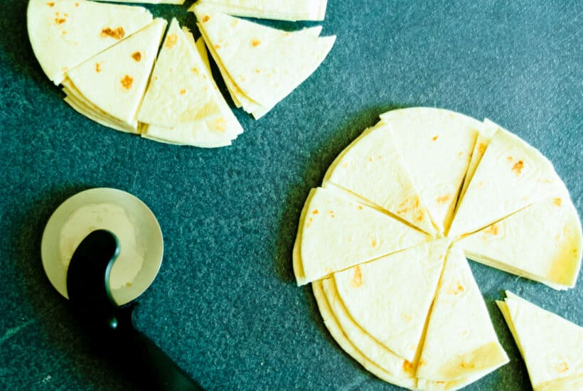 cut tortillas on a blue background with a pizza cutter