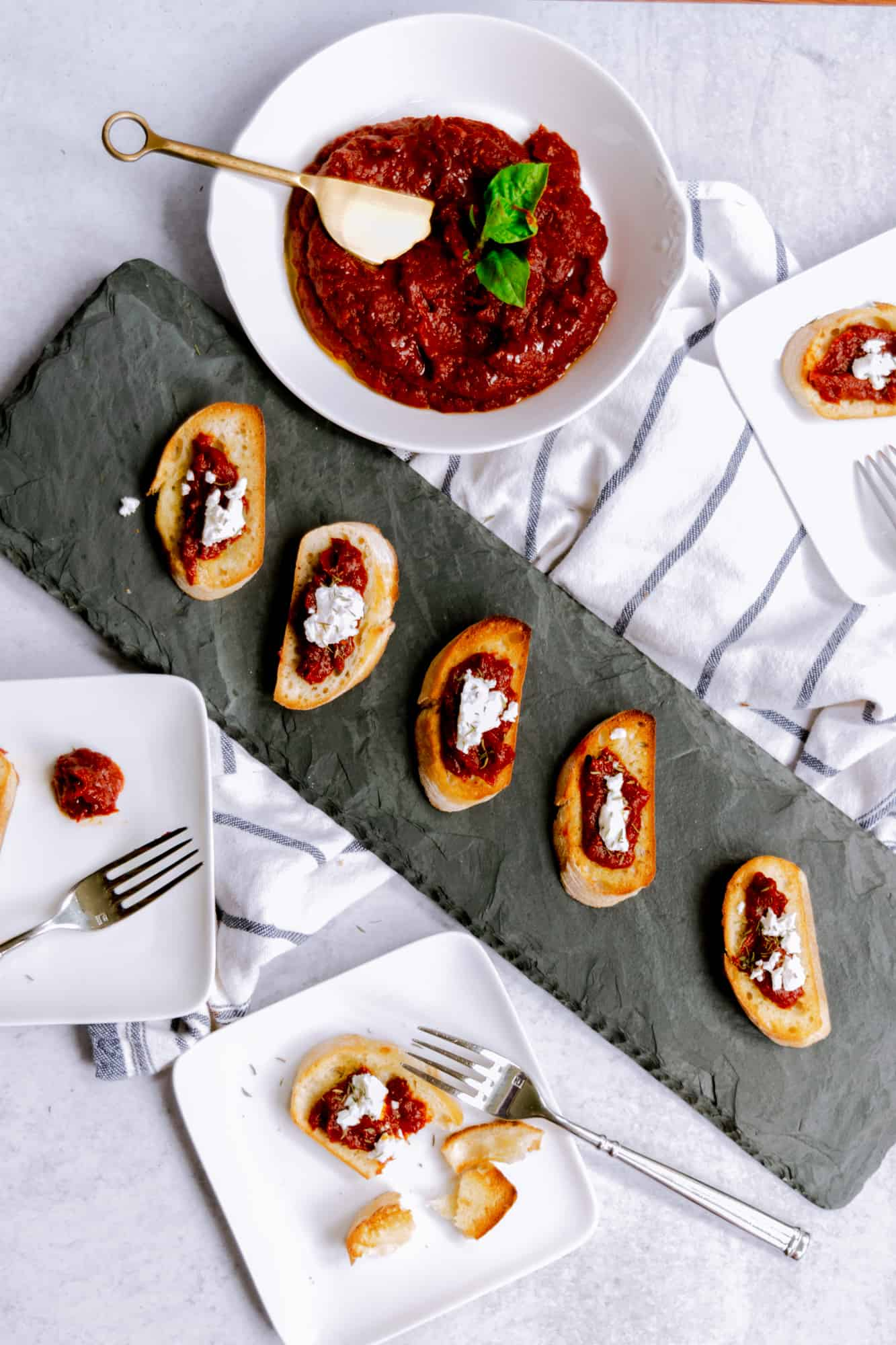 white bowl with tomato jam and black slate board with crostini, jam and goat cheese and white plates with crostini