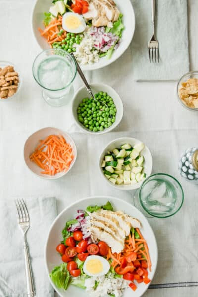a tablescape with a light blue tablecloth, two bowls of salads, bowls of peas, carrots, zucchini, sesame sticks and glasses of water